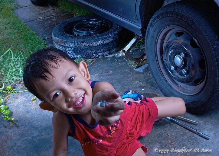 Hafiz sedang membaiki tayar kereta